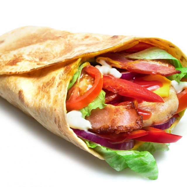 Shawarma sandwich isolated on white background. Gyro fresh roll with pita with grilled chicke, lettuce salad, bacon, tomato, sauces, cheese and vegetables.