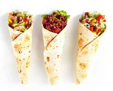 High Angle Still Life of Trio of Tex Mex Fajita Wraps Wrapped in Grilled Flour Tortillas and Filled with Variety of Fillings Such as Chicken, Chili and Shrimp and Fresh Vegetables on White Background